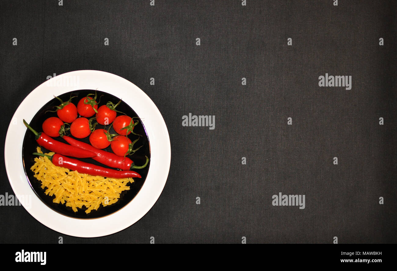 White and black plates with tomatoes, hot chili peppers and pasta, copy space, minimalist style, top view - Stock Image