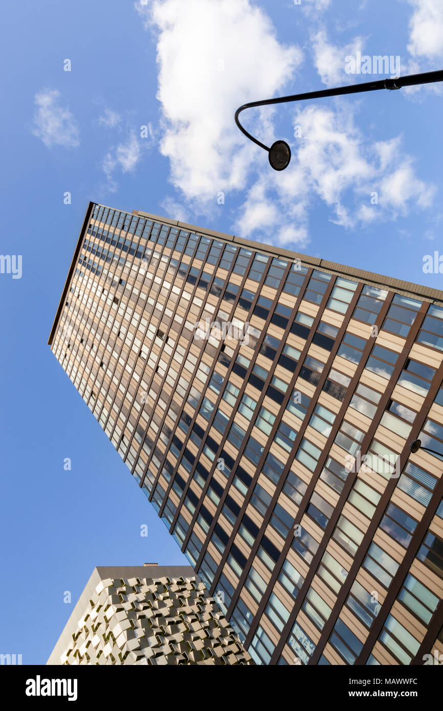 Looking up from the street to the top of a tall building seen against a blue sky with clouds. A modern high rise tower block in Sheffield, England, UK - Stock Image