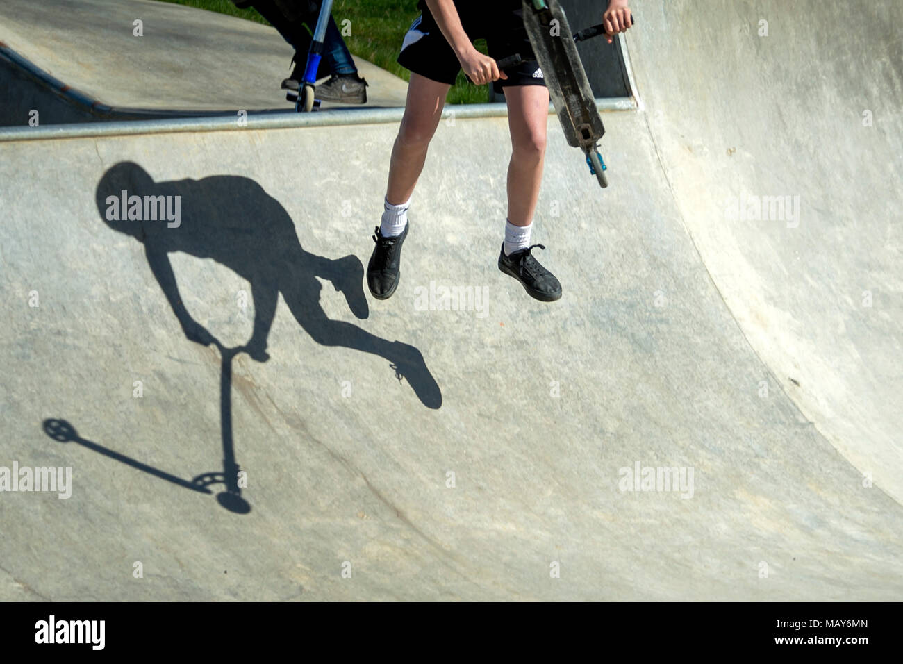 Melton Mowbray, UK. 05th April  2018: UK Weather: A scoot rider casts a shadow on the quarter pipe at playclose  skatepark during half term, blue sky and light warm wind. Credit: Clifford Norton/Alamy Live News. - Stock Image