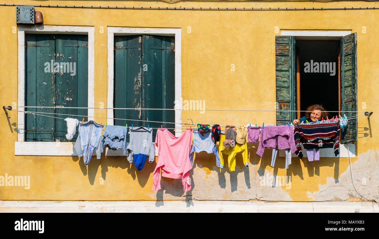 Older woman inspects linen drying on ropes stretched outside her windowStock Photo
