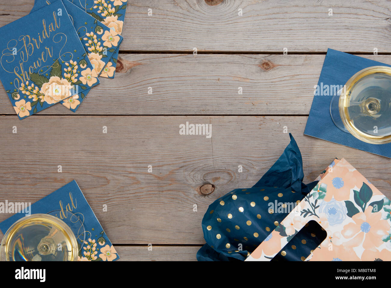 blue floral rustic bridal shower table decorations with wine glass and gift bag on wooden background