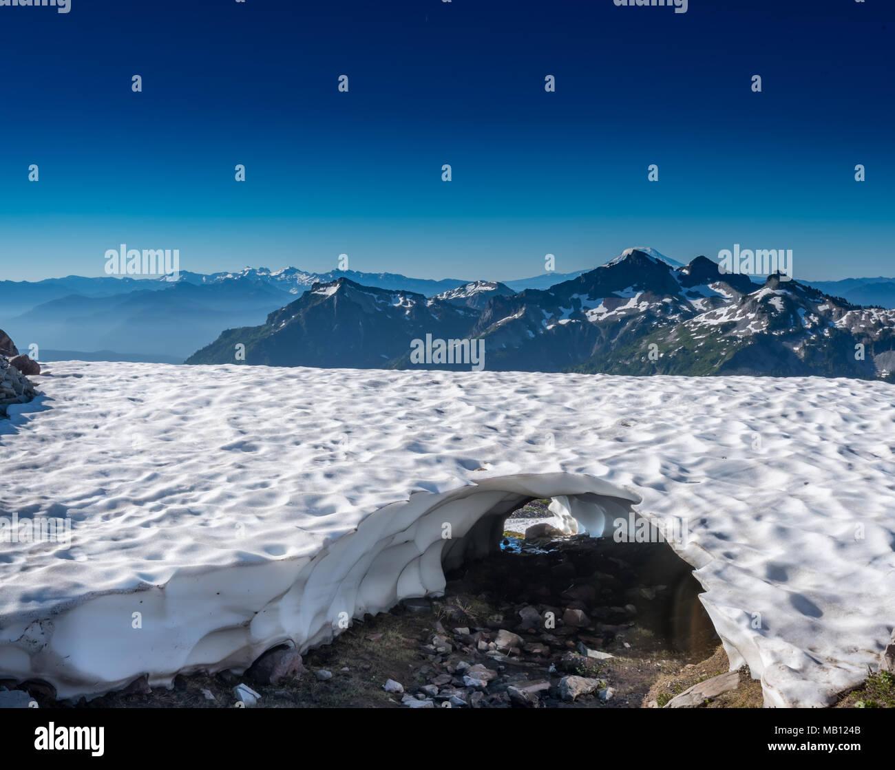 Stream Carves a Tunnel Through Snow Shelf - Stock Image