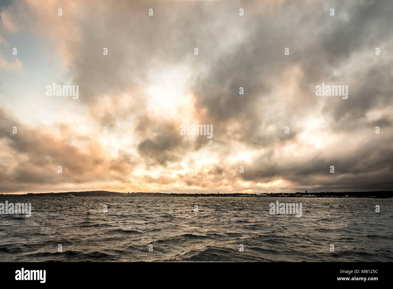 Sun Lights Up Clouds Over Harbor in Maine - Stock Image