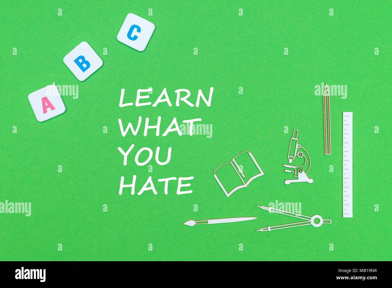 concept school, text learn what you hate, school supplies wooden minitures, abc letters on green backboard - Stock Image