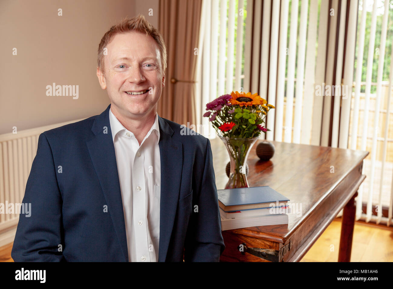 A man in business dress sitting by a table - Stock Image