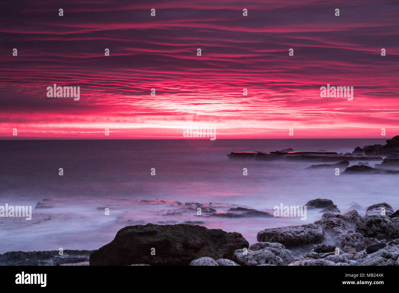 Trow Point, UK. 6th April, 2018. The sun rises on a Cloudy morning looking out over the North Sea.   Credit: Dan Cooke/Alamy Live News - Stock Image