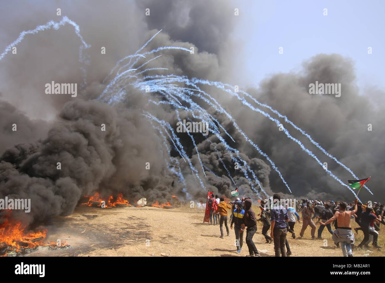 Gaza. 6th Apr, 2018. Palestinian protesters run for cover from tears gas canisters fired by Israeli troops during clashes on the Gaza-Israel border, east of Gaza City on April 6, 2018. Hundreds of Palestinian demonstrators began Friday to set fire to dozens of car tires near the border between eastern Gaza Strip and Israel in a bid to make a shield of black smoke to protect themselves from Israeli soldiers' gunfire. Credit: Khaled Omar/Xinhua/Alamy Live News - Stock Image