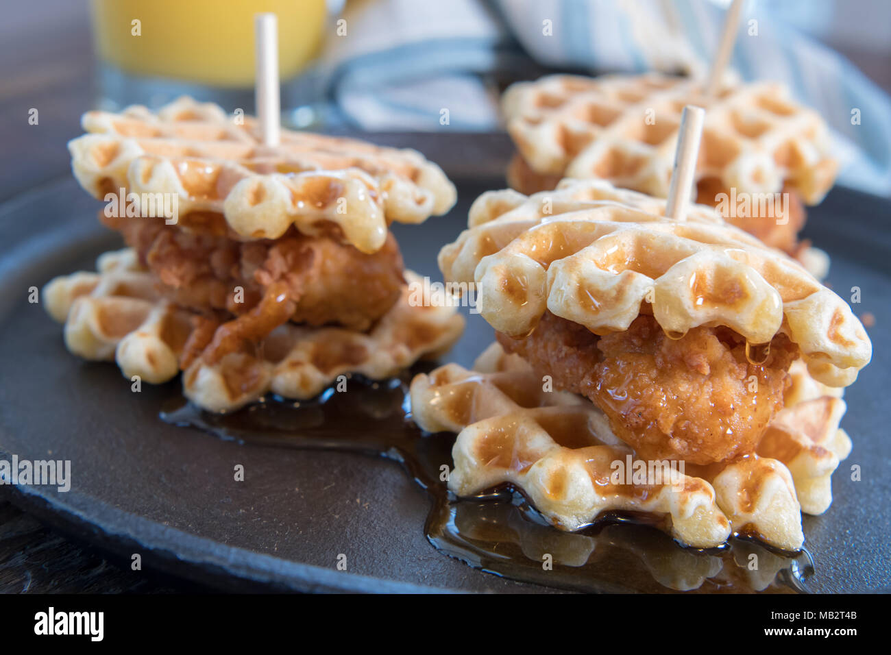 Three Chicken And Waffle Sliders with Syrup on cast iron skillet - Stock Image
