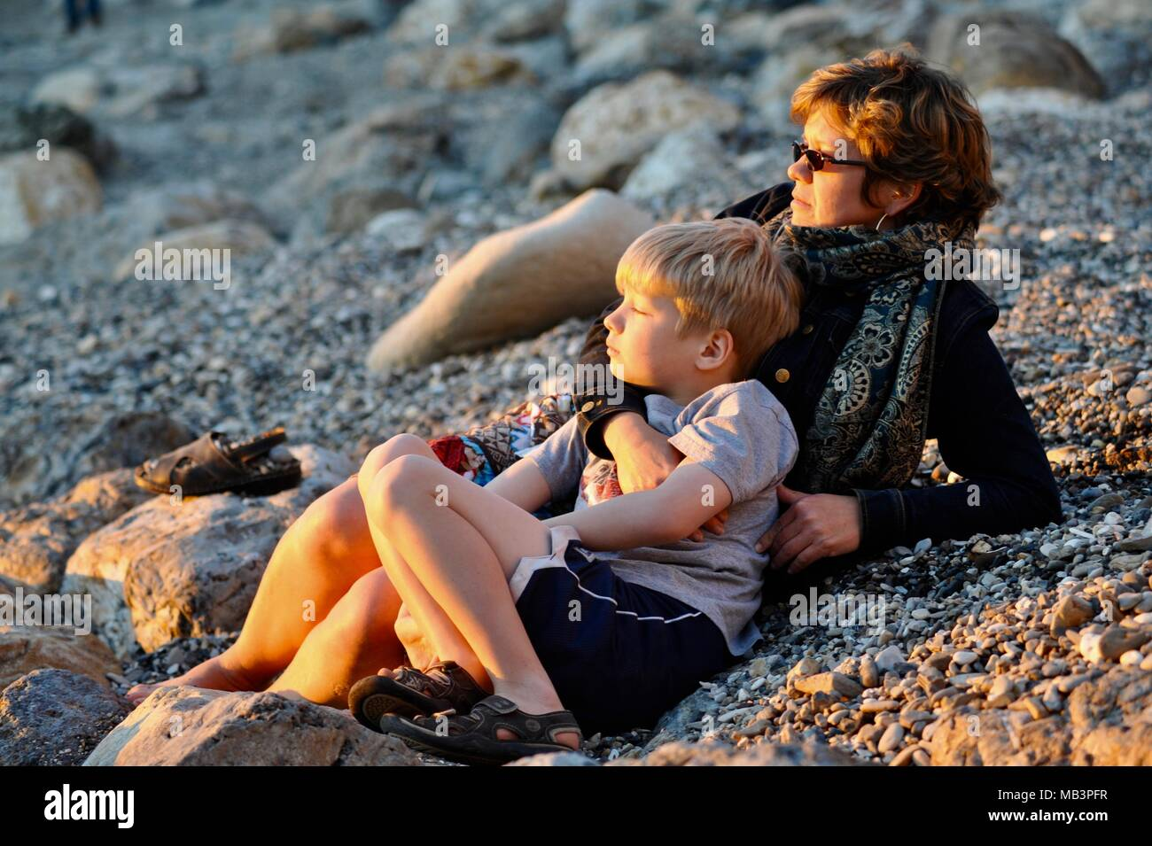 Mother and young son watching sunset from rocky beach outside Pismo Beach, California, USA - Stock Image