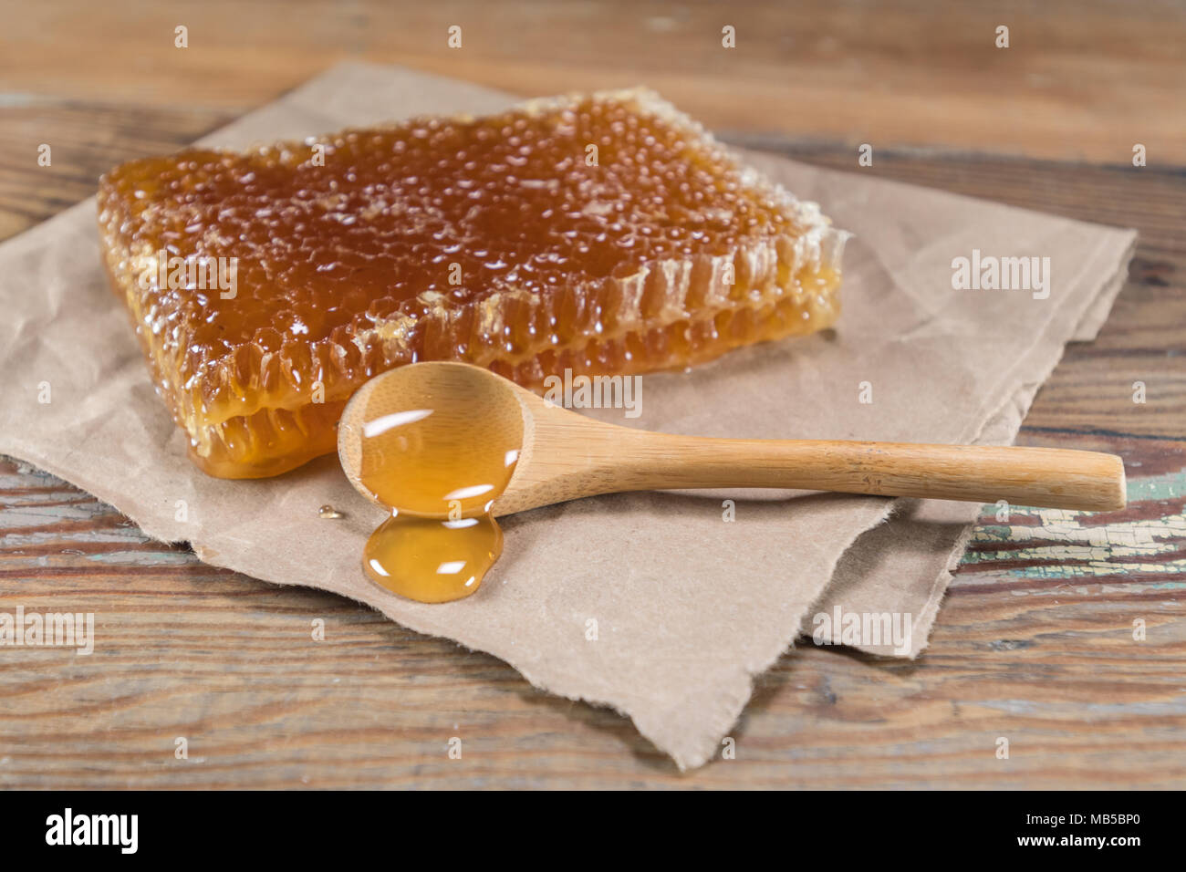 Angle View of Spoon Spilling Honey on Brown Paper - Stock Image