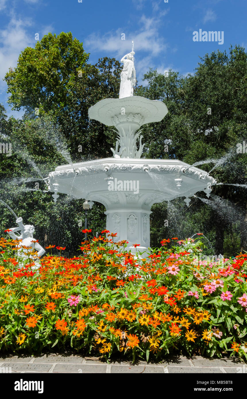 A large marble fountain is surrounded by brightly colored flowers - Stock Image