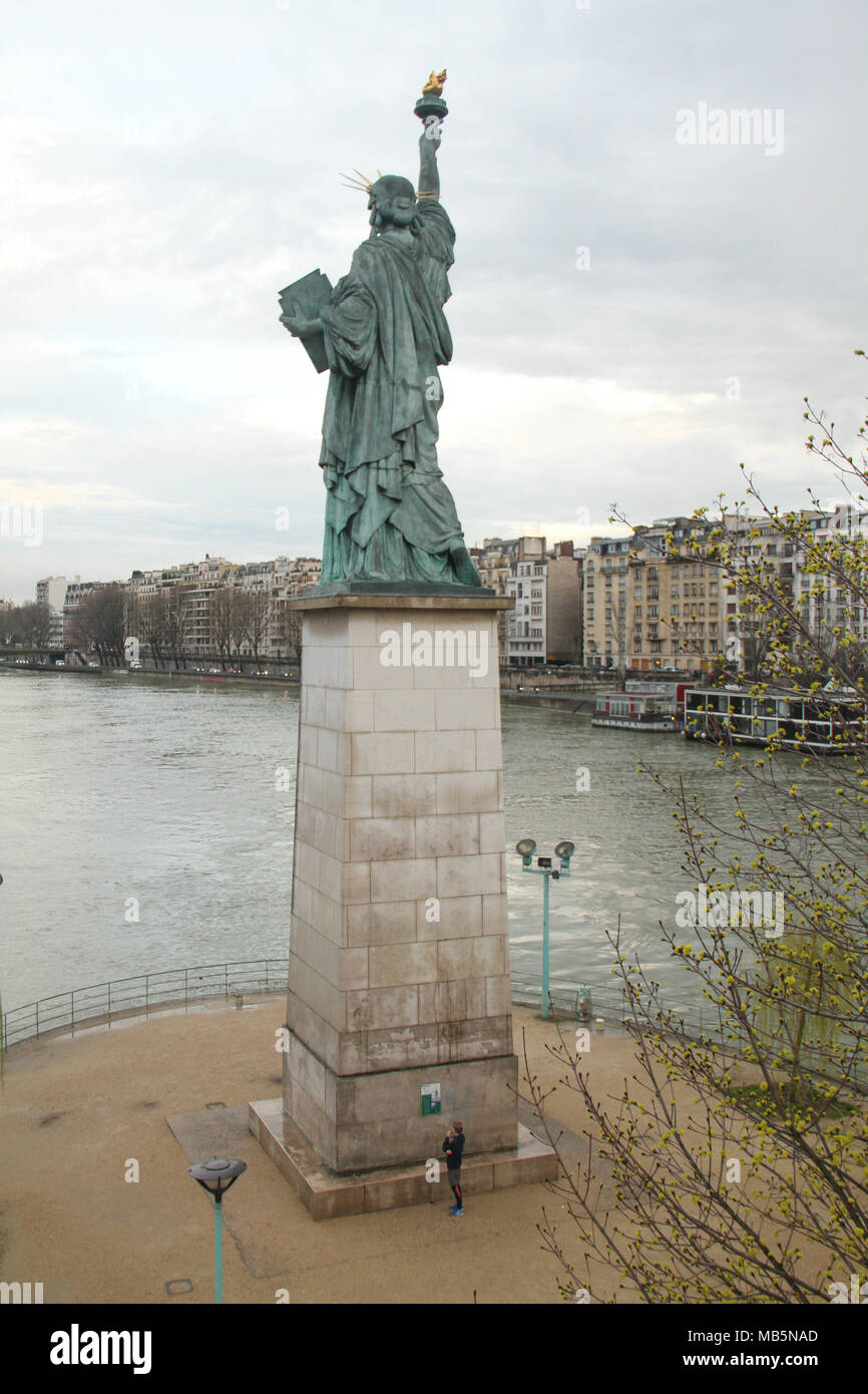 Paris, France -  04 April, 2018. A runner seen below the replica of the Statue of Liberty near the Grenelle Bridge on the Île aux Cygnes in Paris, France on 04 April 2018. This statue was given in 1889 to France by U.S. citizens living in Paris to celebrate the French Revolution three years after the main statue in New York was inaugurated. @ David Mbiyu/Alamy Live News - Stock Image