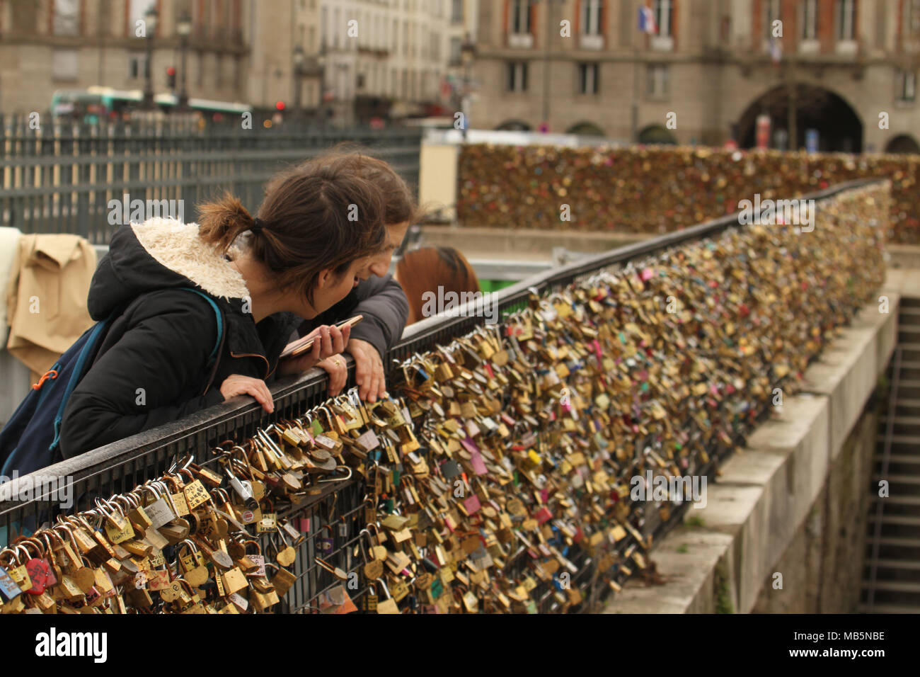 Paris, France -  03 April 2018. People admire a bridge covered in padlocks on the bridge at Pont Neuf on 03 April 2018.  The first Iron bridge built in France, had its railings replaced with glass panels after they collapsed under the weight on the metal padlocks and this culture has cropped up in other bridges in Paris. General view of Paris, France. @ David Mbiyu/Alamy Live News - Stock Image