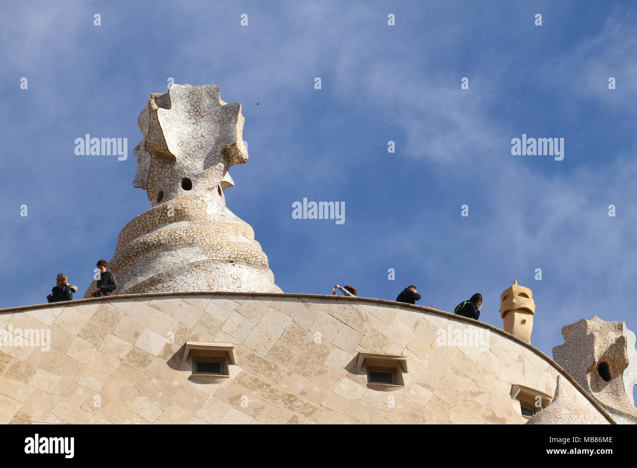 Barcelona, Spain -  31st March 2018. Tourists seen by chimneys on the Casa Mila on 31 March. The modernist building in Barcelona, Catalonia, by architect Antoni Gaudi Barcelona was built between 1906 and 1912.. General view of Barcelona, Spain. @ David Mbiyu/Alamy Live News - Stock Image