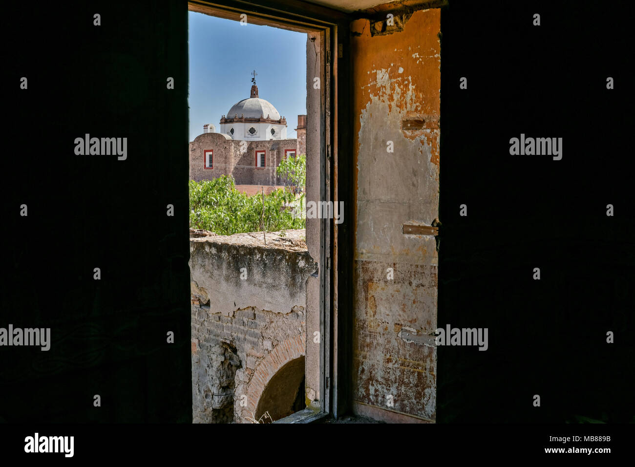 The Iglesia de San Diego De Alcalá as seen from a window in the Hacienda de Jaral de Berrio in Jaral de Berrios, Guanajuato, Mexico. The abandoned Jaral de Berrio hacienda was once the largest in Mexico and housed over 6,000 people on the property. - Stock Image