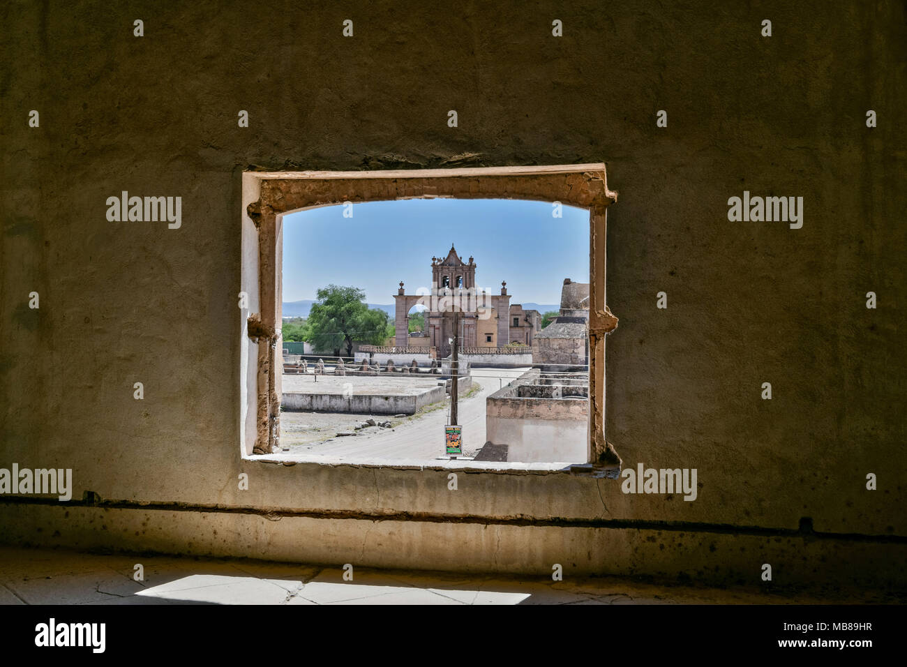 A view of the Moncado Burial Chapel from inside a crumbling room at the fading Hacienda de Jaral de Berrio in Jaral de Berrios, Guanajuato, Mexico. The abandoned Jaral de Berrio hacienda was once the largest in Mexico and housed over 6,000 people on the property and is credited with creating Mescal. - Stock Image