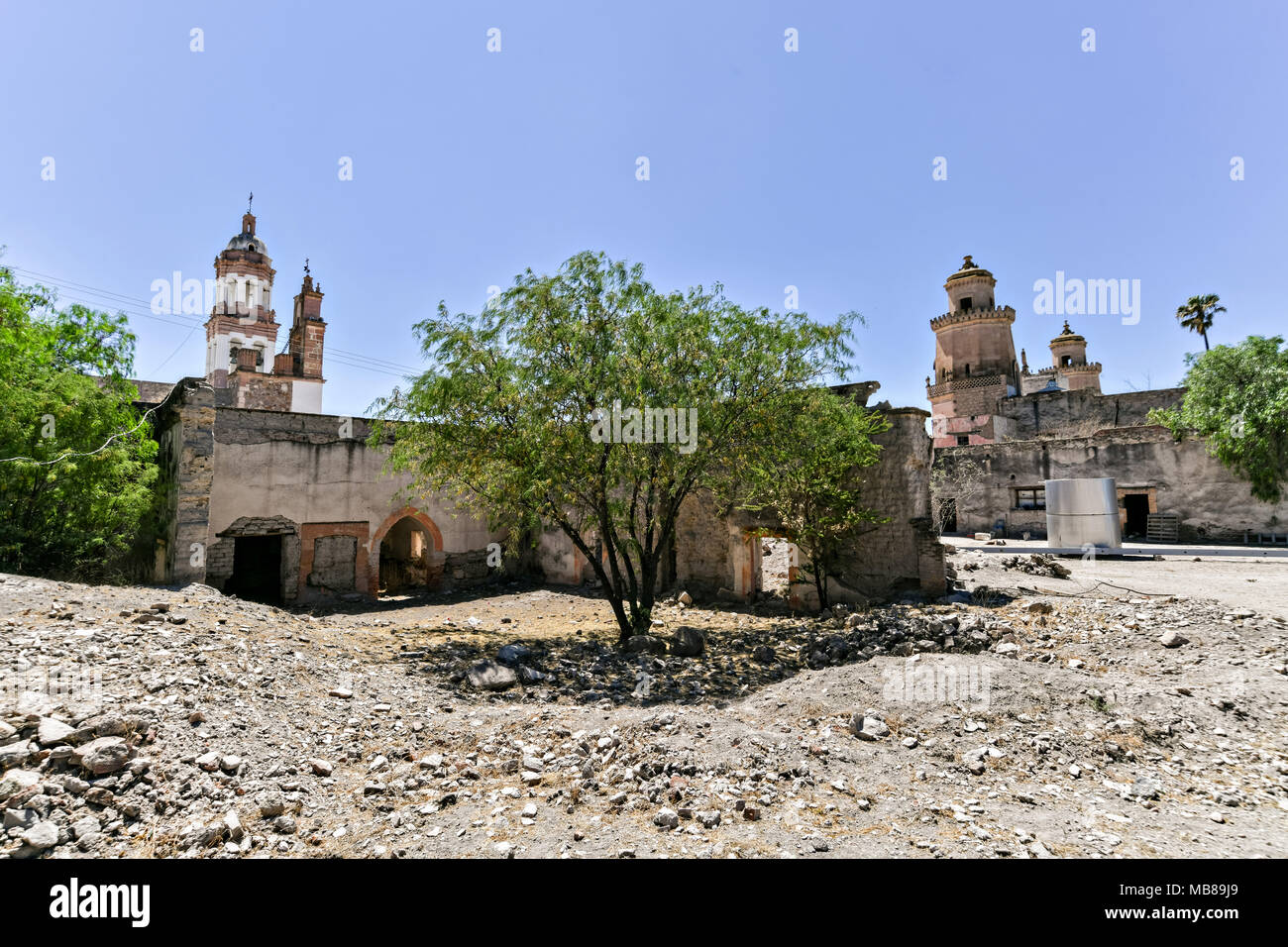 The ruins of a courtyard looking toward the front at the fading Hacienda de Jaral de Berrio in Jaral de Berrios, Guanajuato, Mexico. The abandoned Jaral de Berrio hacienda was once the largest in Mexico and housed over 6,000 people on the property and is credited with creating Mescal. - Stock Image