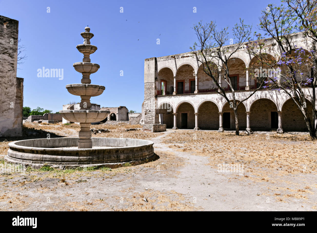 A secondary courtyard and fountain at the fading Hacienda de Jaral de Berrio in Jaral de Berrios, Guanajuato, Mexico. The abandoned Jaral de Berrio hacienda was once the largest in Mexico and housed over 6,000 people on the property and is credited with creating Mescal. - Stock Image