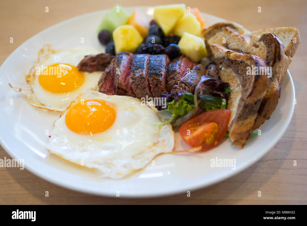 Steak eggs for breakfast at Hometown Diner in Saskatoon, Canada. Medium rare flank steak, sunny side up eggs, marble rye toast, and fruit pictured. - Stock Image