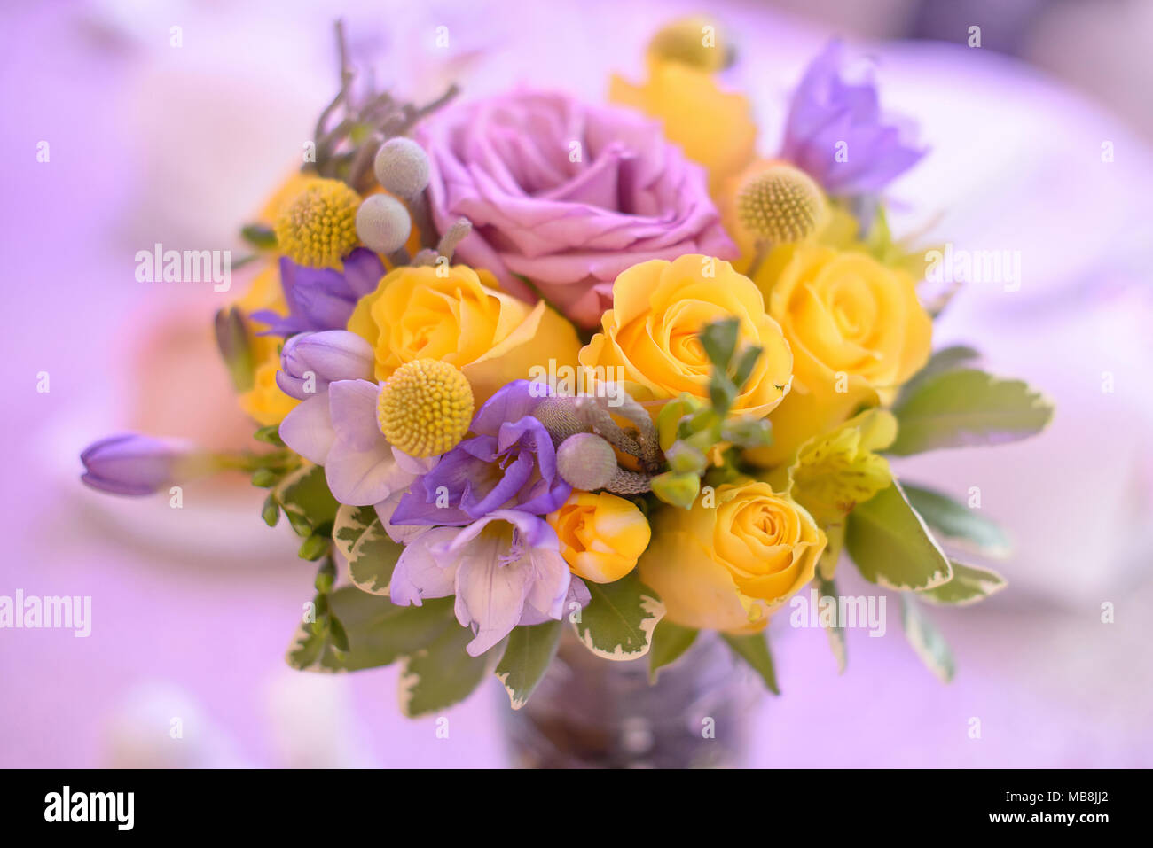 Fancy Colored Floral Arrangement With Bright Yellow And Purple Roses