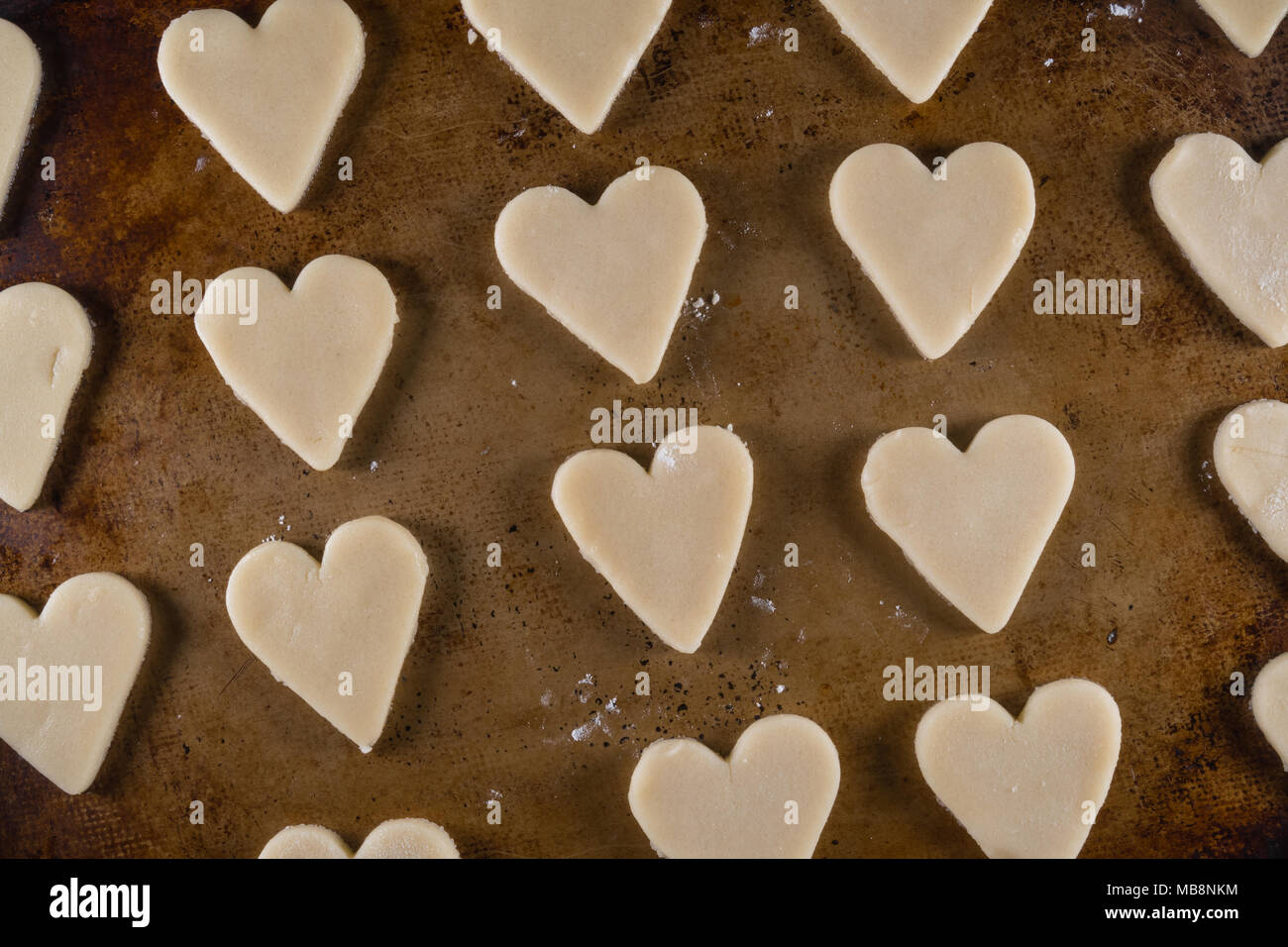 Close Up of Heart Shaped Cookie Dough on Sheet Pan - Stock Image