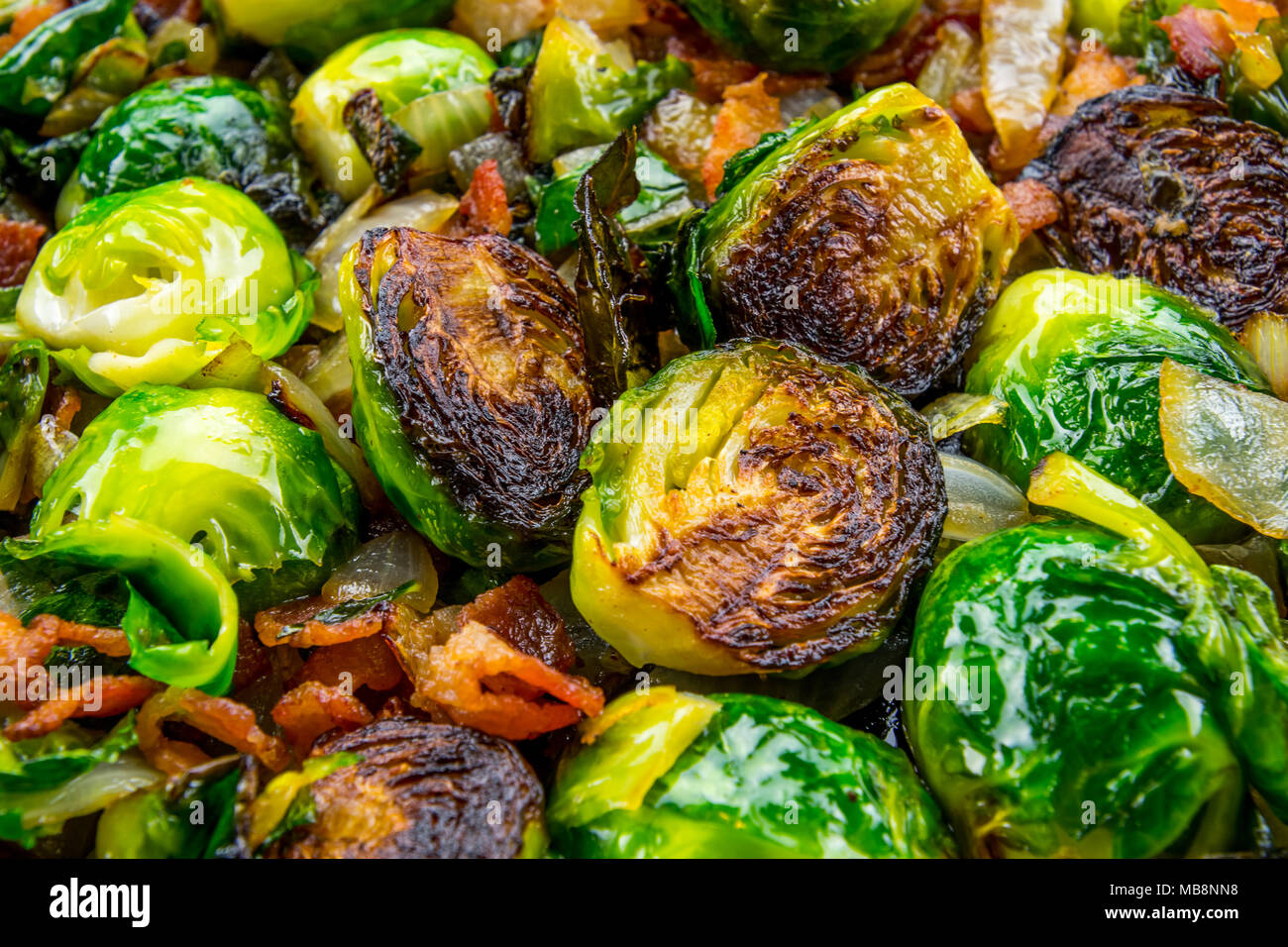 Close up of Roasted Brussels Sprouts with bacon and onion - Stock Image