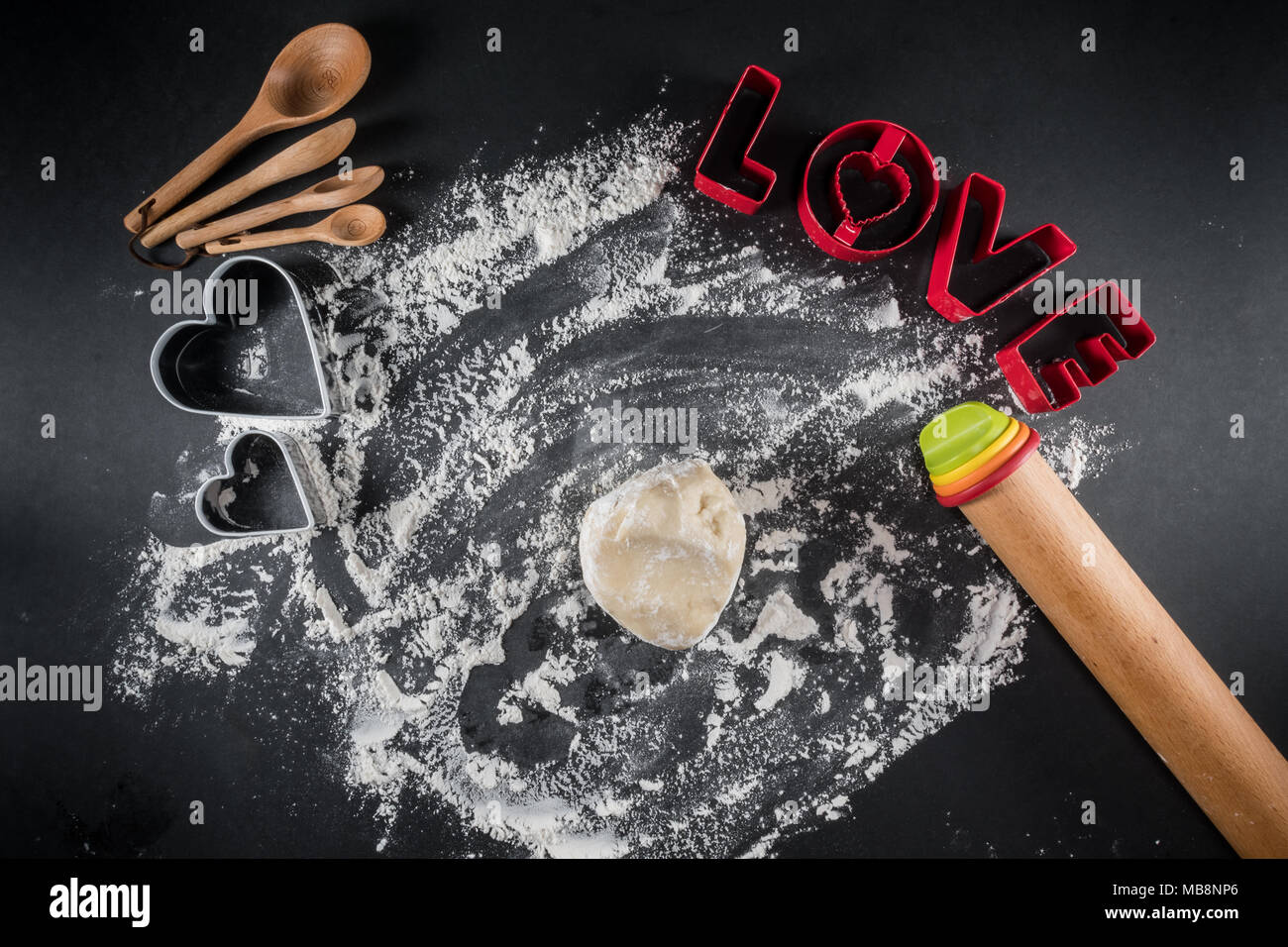 Cookie Dough Ball and Love Cookie Cutters on floured surface - Stock Image