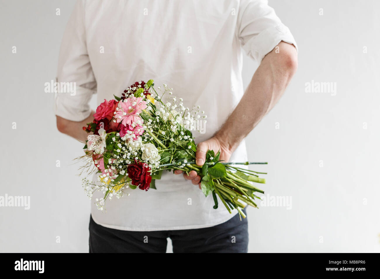 Elegant Man Holding A Bouquet Of Spring Flowers Behind His Back For