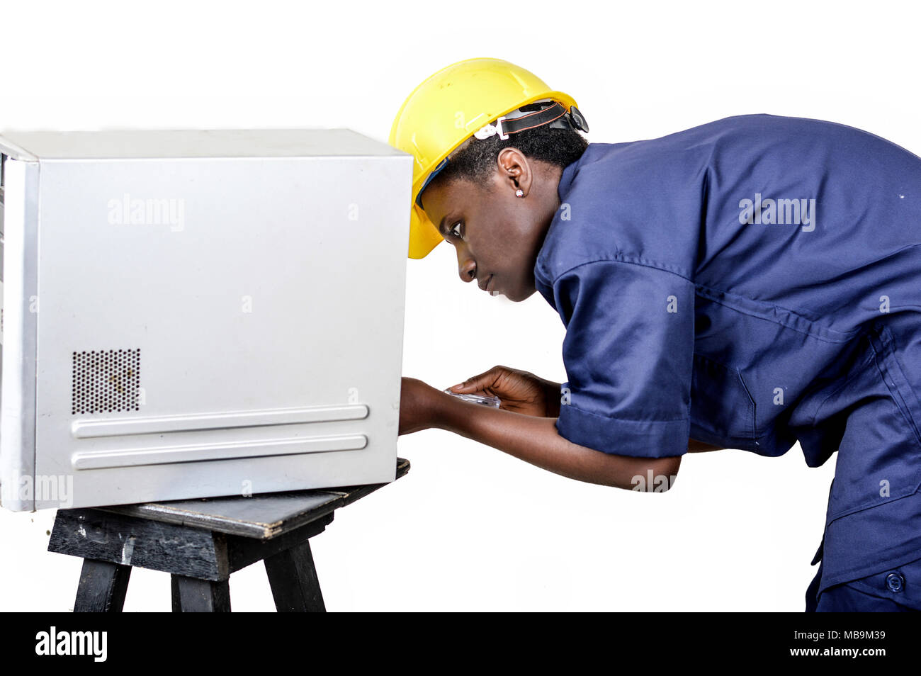 Young African woman in computer maintenance opens the central unit with a turning - Stock Image