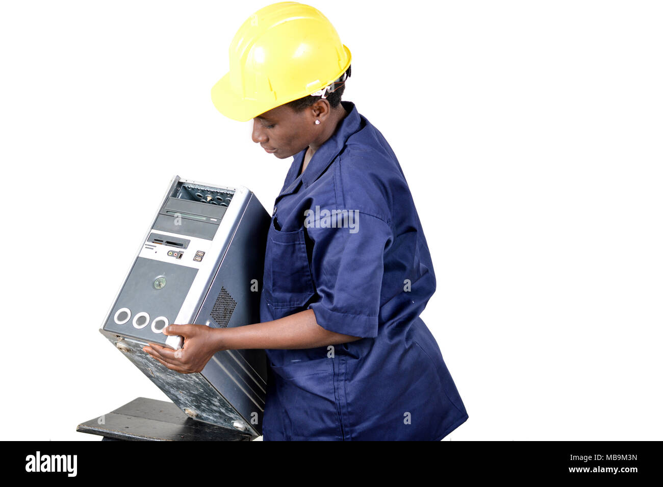 Young female computer repairer checks a central unit by lifting it. - Stock Image