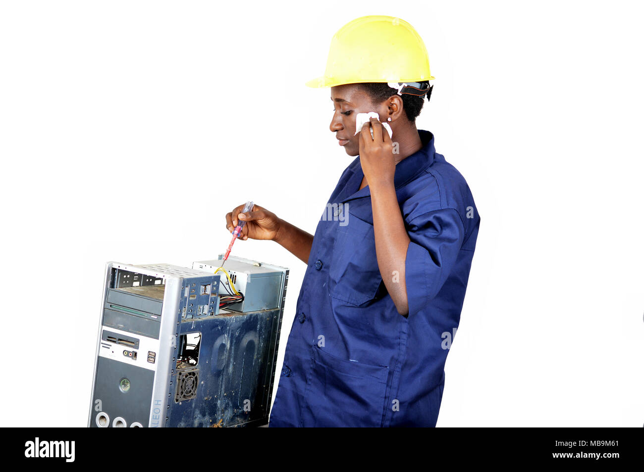Young woman doing the maintenance of a desktop by wiping the face with a pocket - Stock Image