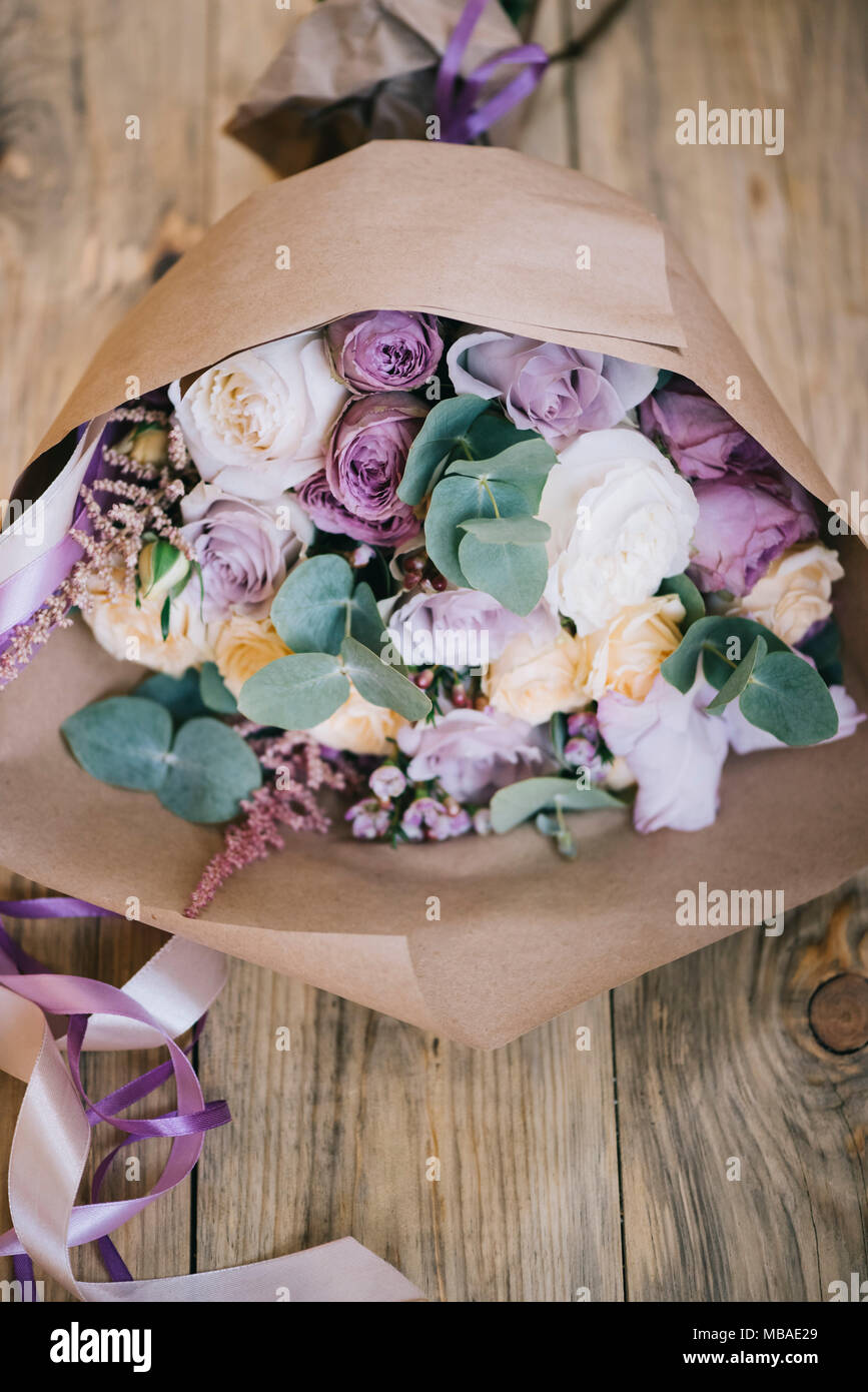 Beautiful fresh flower bouquet with eucalyptusroses and english beautiful fresh flower bouquet with eucalyptusroses and english roses packed in craft paper on the old wooden table background izmirmasajfo