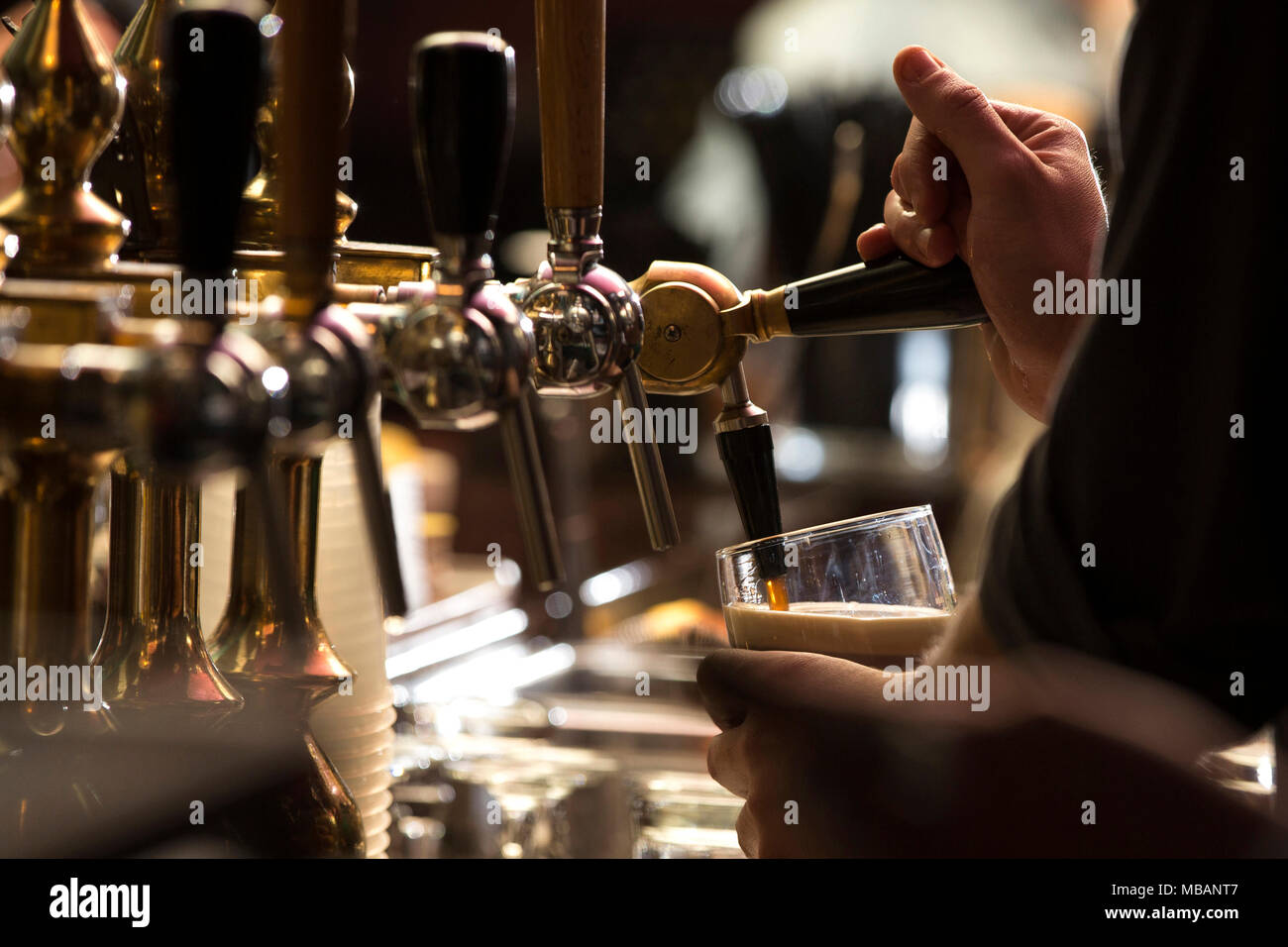 closeup of a bartender pouring a dark stout beer in tap with subject and focus on the rightStock Photo