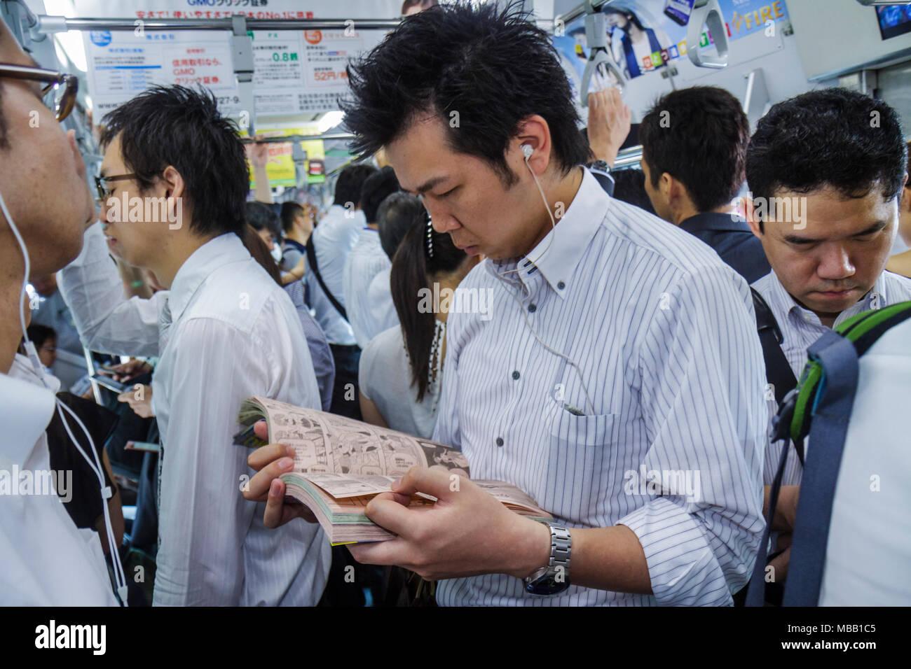 Tokyo Japan Yurakucho JR Yurakucho Station Yamanote Line Asian man crowded standing commuters train car strap holders reading co - Stock Image