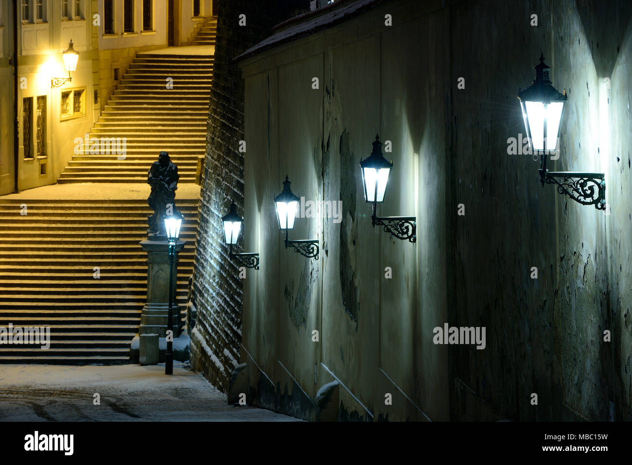 Snowy winter season. Detail of wall with lamps. Night stairs leading to St. Vitus cathedral. Hradcany, Prague, Czech republic - Stock Image