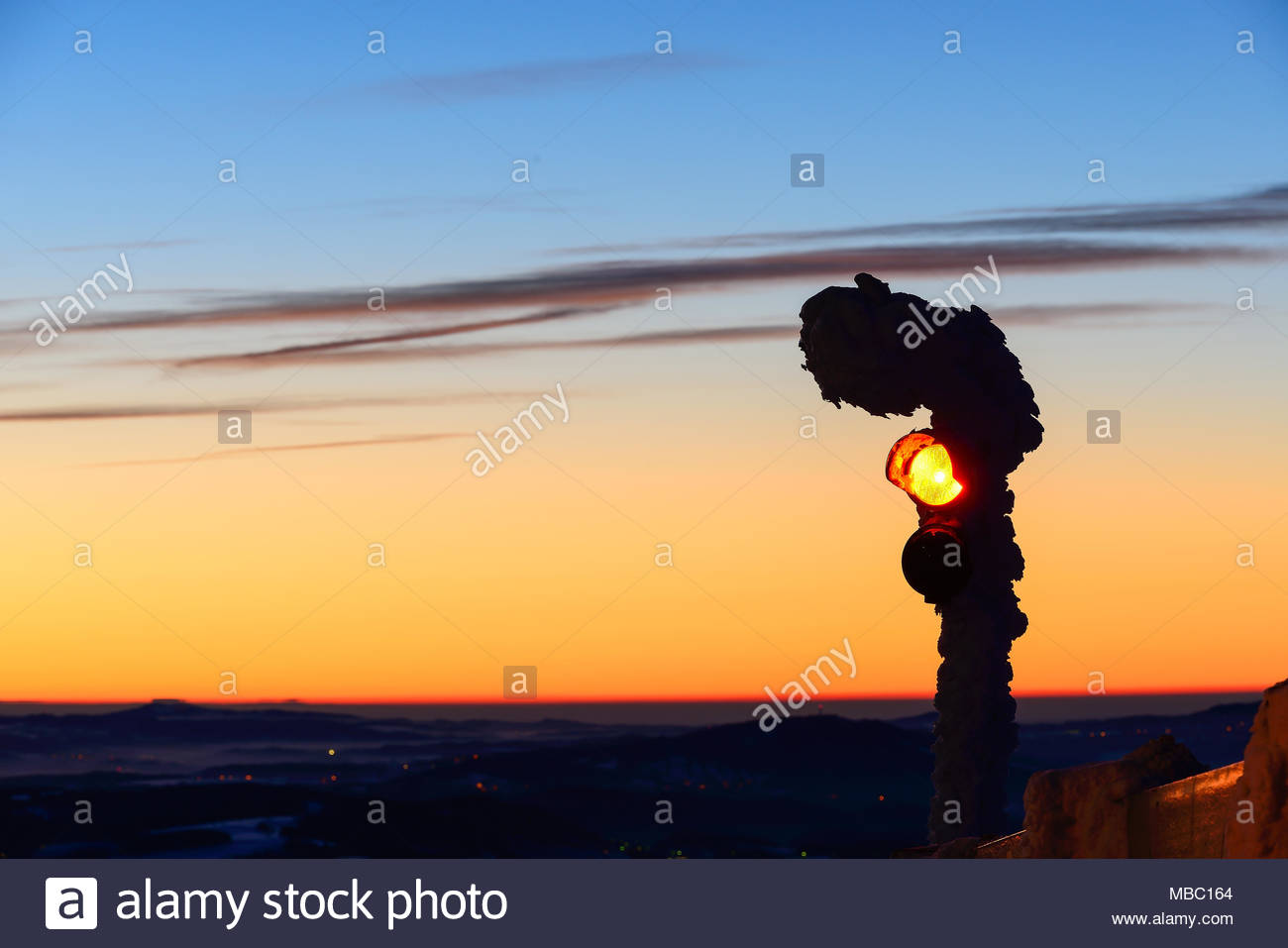 Traffic light at Jested mountain peak. Cold morning near town Liberec. Winter mountain morning before sunrise. Snowy detail if red light. Jizerske hor - Stock Image