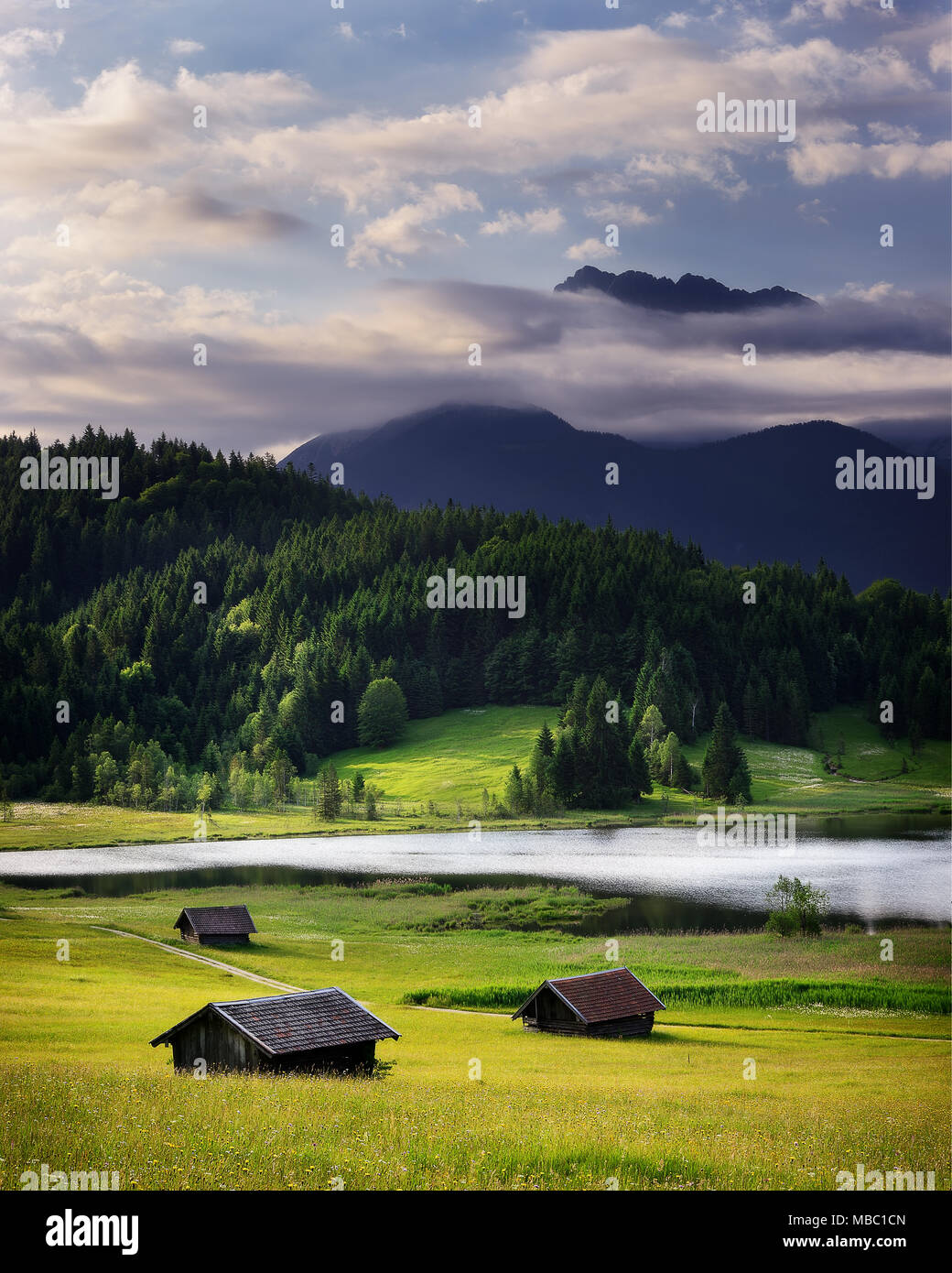 Geroldsee view during summer day with foggy sunrise. Rainy cloudy sky and huts in mountains near beautiful lake. Bavarian Alps, Bavaria, Germany. - Stock Image