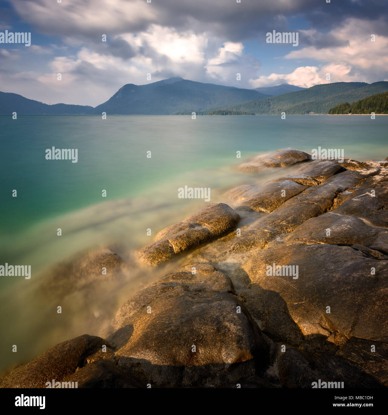 Amazing autumn scenery ar Walchensee lake. Calm water with beach rocks and heavy rainy clouds over alpine peaks. Walchensee, Bavaria, Germany. - Stock Image