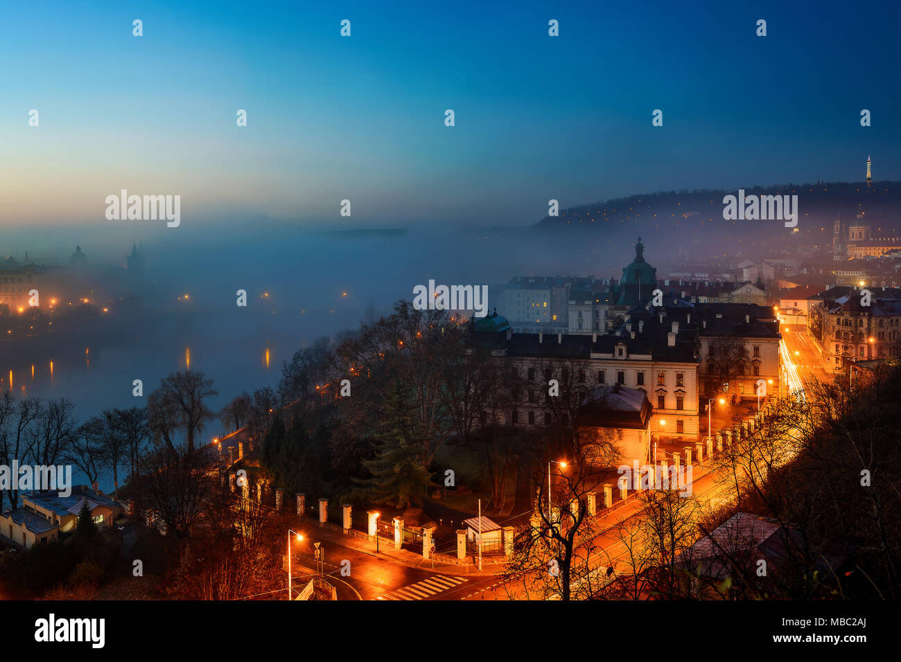 Amazing foggy sunrise. Beautiful morning view at old city downton. Typical autumn view at Chrles bridge, Prague, Czech republic - Stock Image