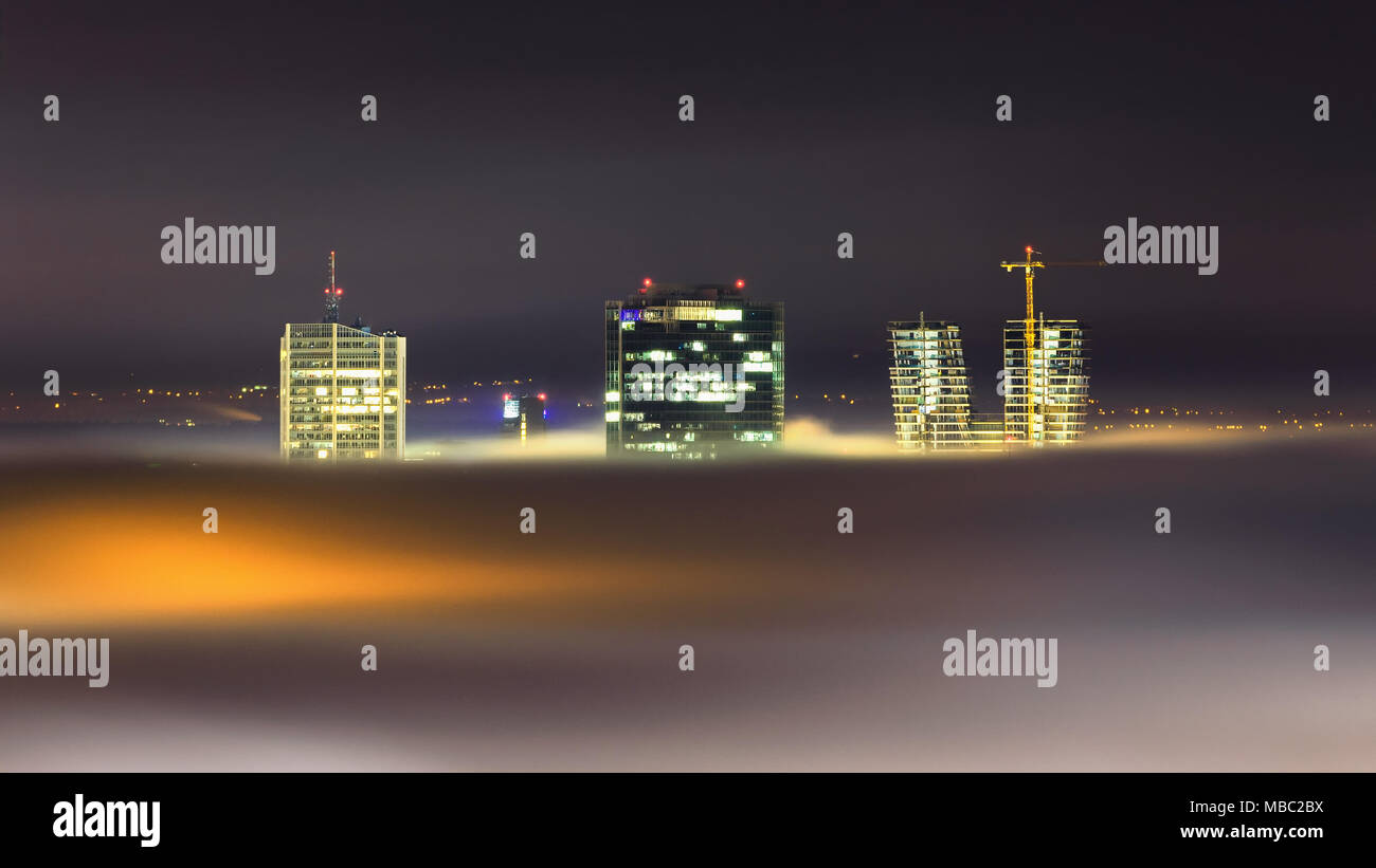 Night view at skyscrapers with foggy waves over city, Prague, Czech republic - Stock Image