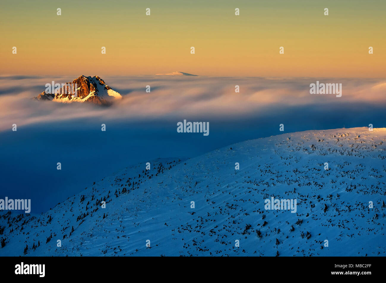 Amazing foggy sunset at mountain peak during cold winter day in Lesser Fatra, Slovakia - Stock Image