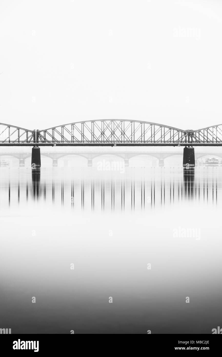 Foggy winter mood at Vltava river. Reflection of bridges in water. Detail of train bridge. Black and white atmosphere, Prague, Czech republic - Stock Image