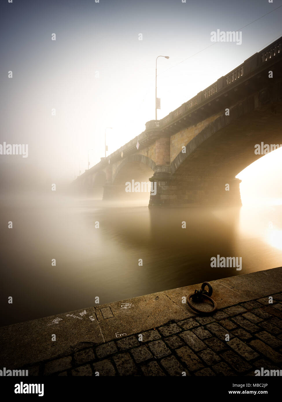 Morning view at Palacky bridge. Historical bridge over Vltava river. Foggy sunlight at riverbank. Typical autumn season. Prague, Czech republic - Stock Image