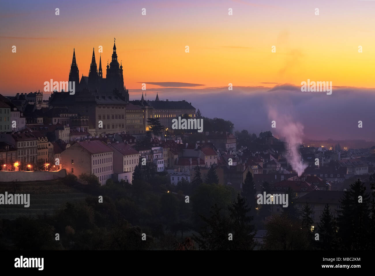 Morning view at Saint Vitus cathedral in Prague. Amazing sunrise foggy detail of gothic castle. Typical spring season city in Czech republic. - Stock Image