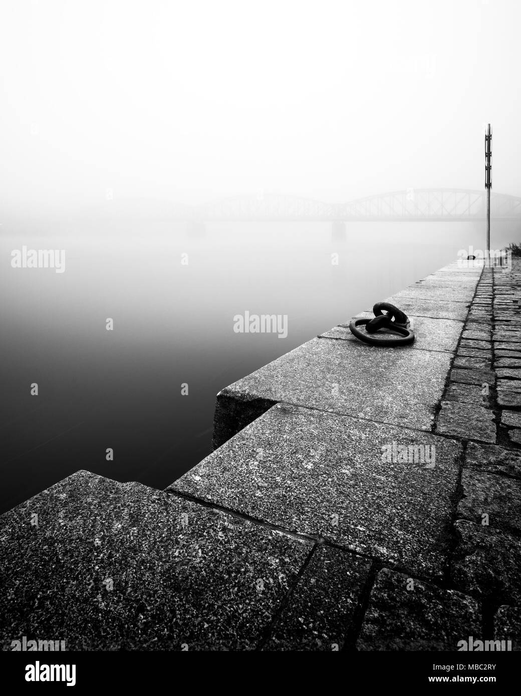 Foggy autumn mood at Vltava river. Reflection of bridge in water. Detail of riverbank. Black and white atmosphere, Prague, Czech republic - Stock Image