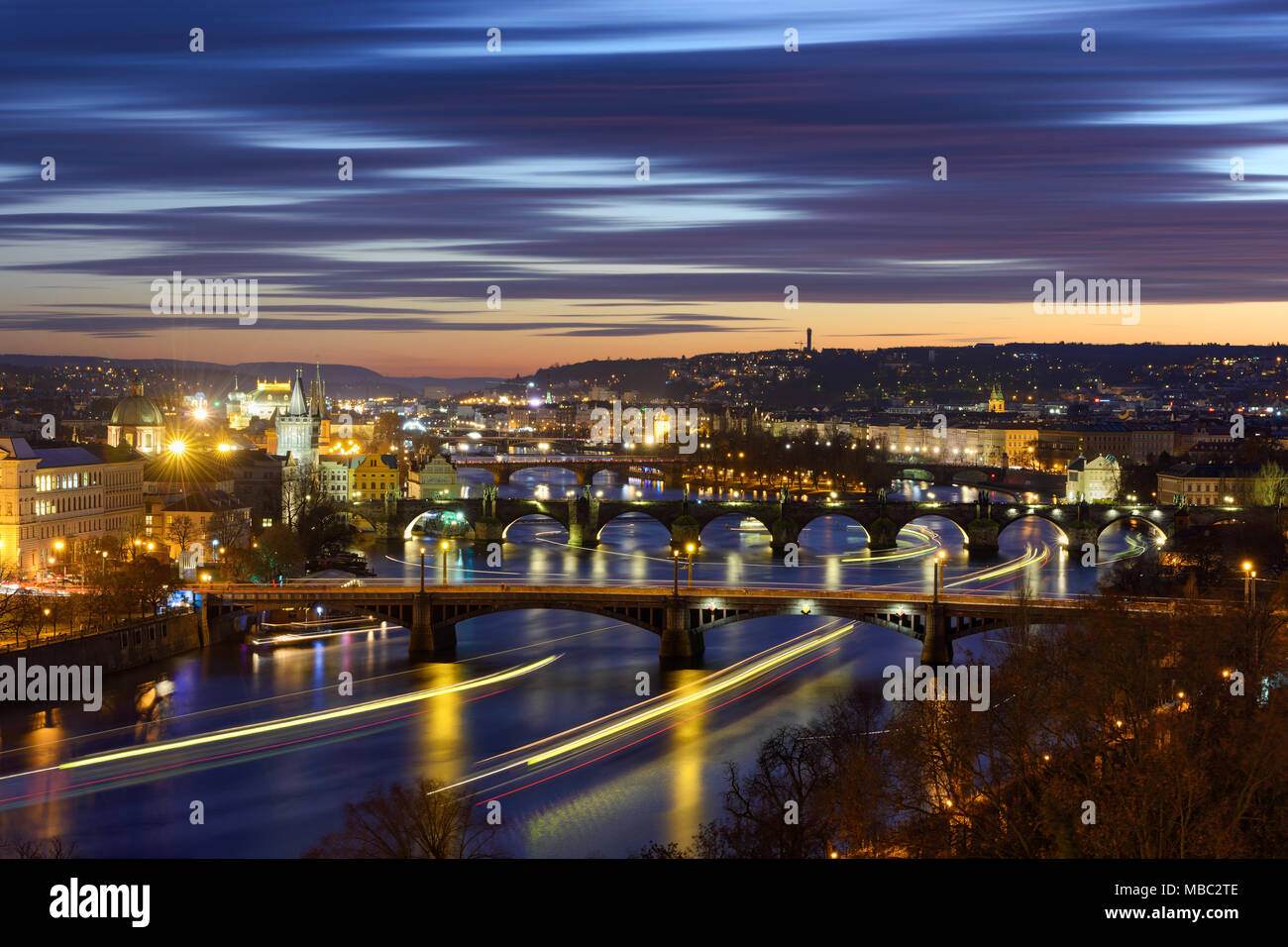 River traffic near majestic Charles Bridge during sunset with several boats, Prague, Czech republic - Stock Image