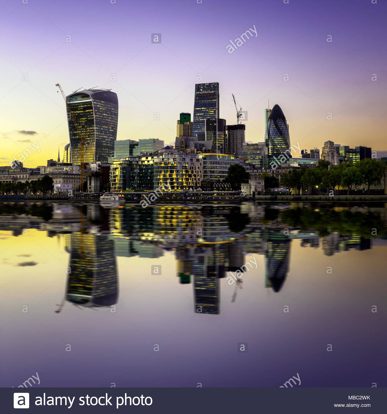 The bank district of central London with famous skyscrapers at sunset with amazing blue sky and reflection, London, United Kingdom - Stock Image