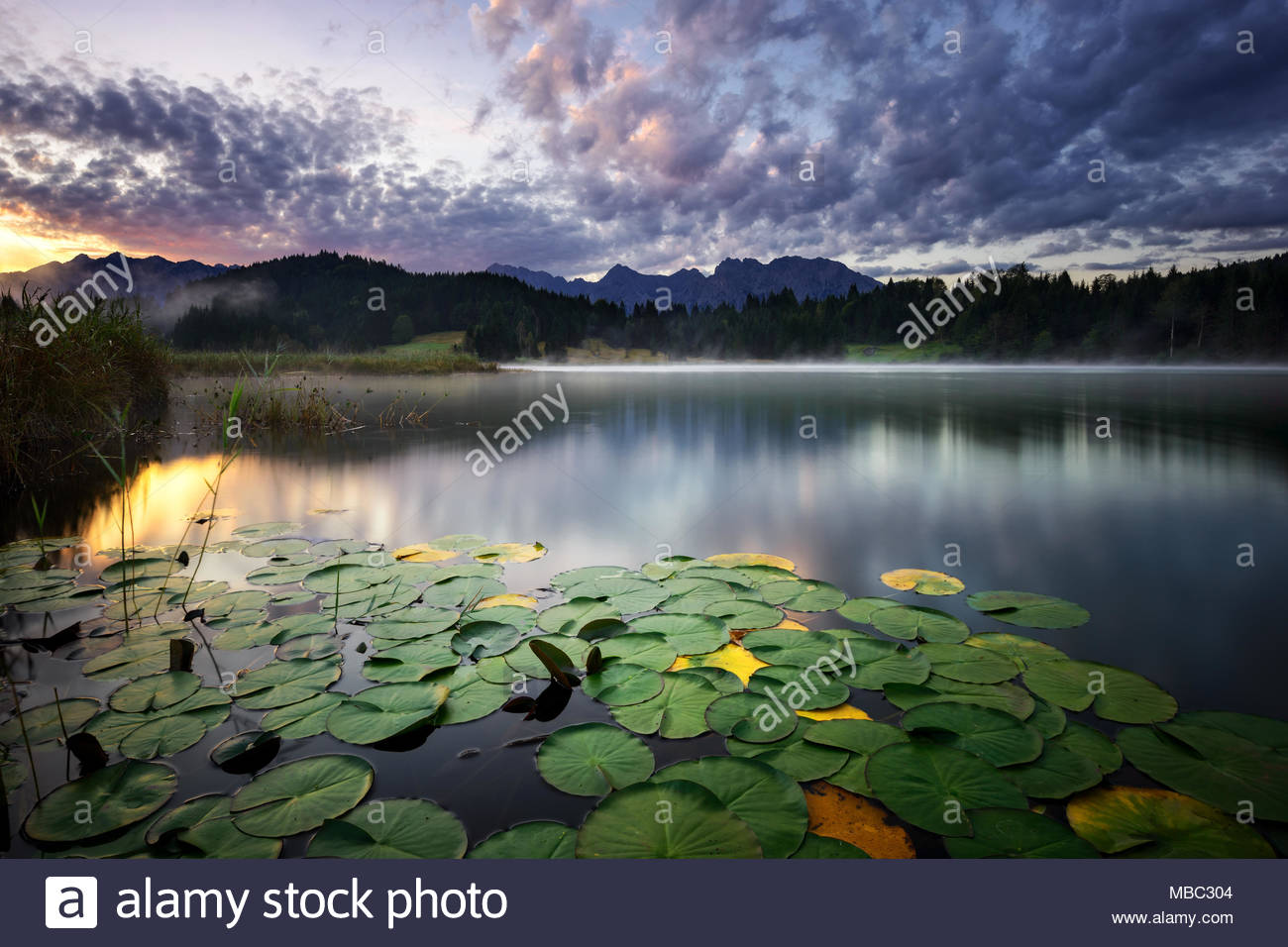 Geroldsee view during autumn with foggy sunrise. Colorful cloudy sky and lake reflection in mountains. Bavarian Alps, Bavaria, Germany. - Stock Image