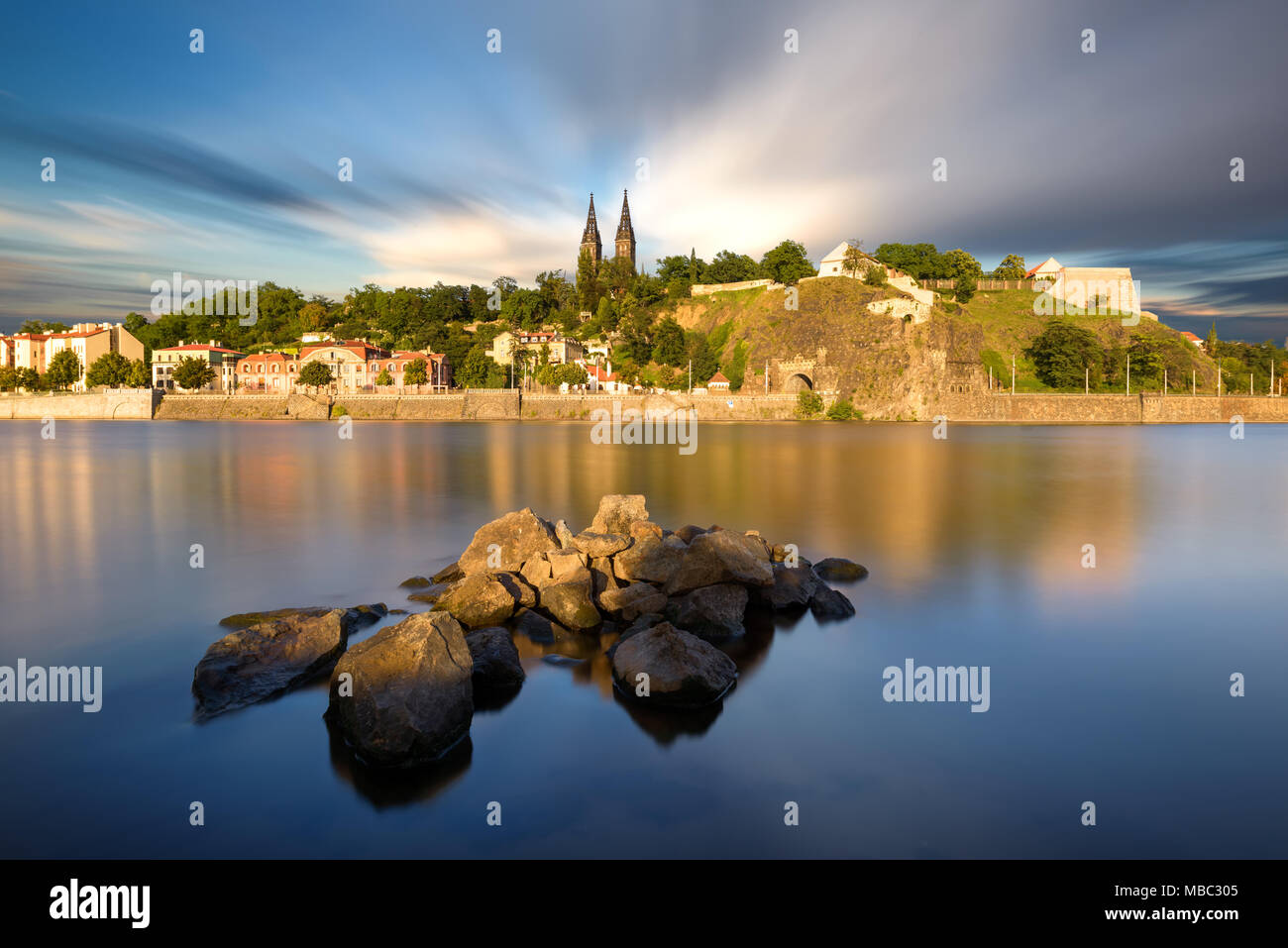 Famous Vysehrad church during sunny day. Amazing cloudy sky in motion. Hot summer season. Typical landscape reflection at Vltava river, Prague, Czech  - Stock Image