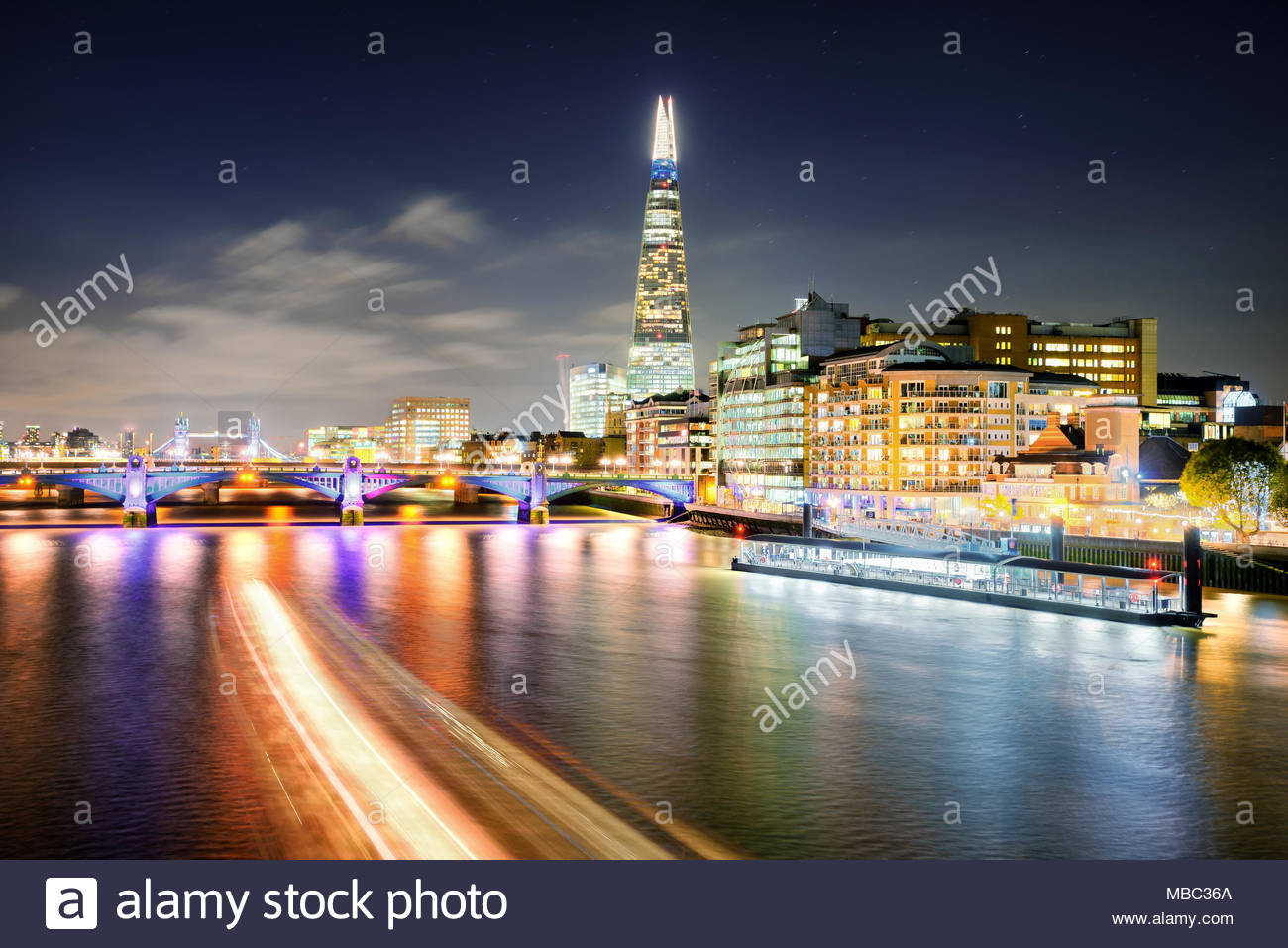 London at night with urban architecture, amazing skyscraper and boat at Thames river, United Kingdom - Stock Image